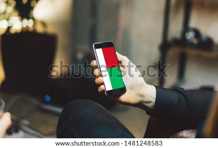 Man holding Smartphone with Flag of Madagascar. Madagascar Flag on Mobile Screen.