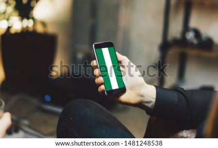 Man holding Smartphone with Flag of Nigeria. Nigeria Flag on Mobile Screen. #1481248538