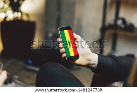 Man holding Smartphone with Flag of Senegal. Senegal Flag on Mobile Screen. #1481247788