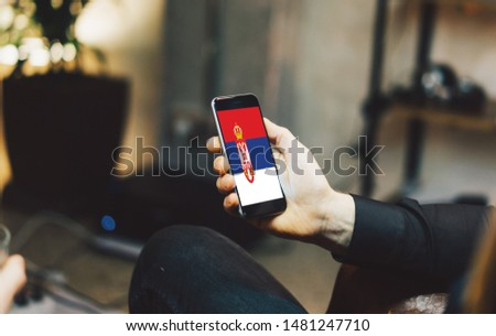 Man holding Smartphone with Flag of Serbia. Serbia Flag on Mobile Screen. #1481247710