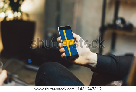 Man holding Smartphone with Flag of Sweden. Sweden Flag on Mobile Screen.