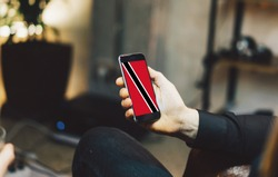 Man holding Smartphone with Flag of Trinidad and Tobago. Trinidad and Tobago Flag on Mobile Screen.