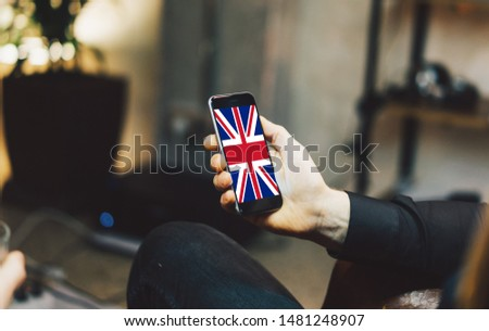 Man holding Smartphone with Flag of United Kingdom. United Kingdom Flag on Mobile Screen.