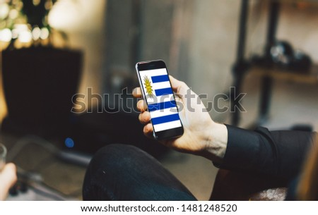 Man holding Smartphone with Flag of Uruguay. Uruguay Flag on Mobile Screen. #1481248520