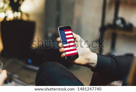 Man holding Smartphone with Flag of USA. USA Flag on Mobile Screen. #1481247740