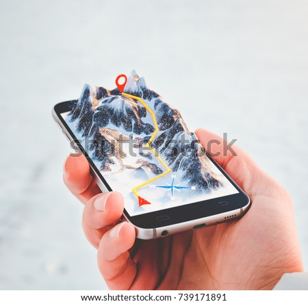 Man holding smartphone with mountains on the screen. Virtual reality. Navigation route concept.