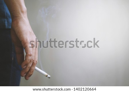 man holding smoking a cigarette in hand. Cigarette smoke spread. dark background