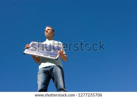 Man holding solar panel against clear blue sky
