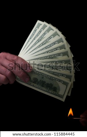 man holding stack of dollars and match fire