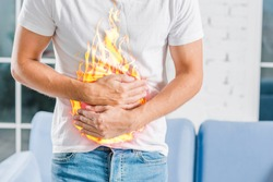 Man holding stomach due to stomach pain and burning