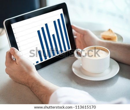 Man holding tablet computer with graphic in cafe