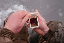 Man holding the box with fishing bait in his hand. Winter fishing on ice. Red bait. Putting bait on the hook. Winter fishing. High quality photo