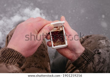 Man holding the box with fishing bait in his hand. Winter fishing on ice. Red bait. Putting bait on the hook. Winter fishing. High quality photo Stock photo ©
