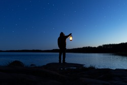 Man holding the old lamp outdoors near the lake. Hand holds a large lamp in the dark. Ancient lantern illuminates the way on a night. Light and hope concept.