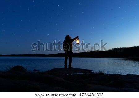 Man holding the old lamp outdoors near the lake. Hand holds a large lamp in the dark. Ancient lantern illuminates the way on a night. Light and hope concept. Photo stock ©