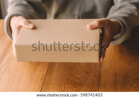 Man holding the package on the table.paper box.Cardboard boxes,vintage effect filter style pictures #598741403
