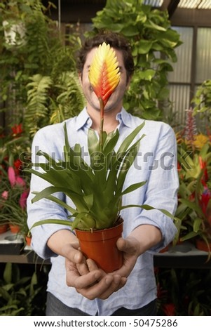 Man holding tropical plant, covering face