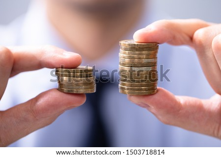 Man Holding Two Coin Stacks To Compare Stockfoto ©