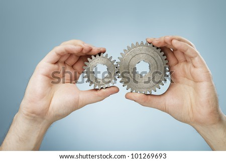 Man holding two different sizes metallic cog gear wheels in his hands.