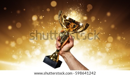 Man holding up a gold trophy cup with abstract shiny background, copy space for text #598641242