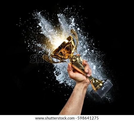 Man holding up a gold trophy cup with powder explosion on background. Concept of success and achievement. isolated on black background #598641275