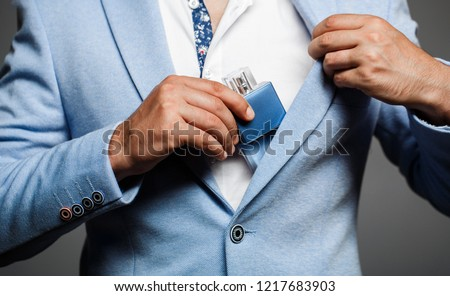 Man holding up bottle of perfume. Men perfume in the hand on suit background. Handsome man in formal suit and with bottle of perfume, closeup. Fashion cologne bottle. Fragrance smell. Men perfumes.