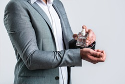 Man holding up bottle of perfume. Men perfume in the hand on suit background. Man in formal suit, bottle of perfume, closeup. Fragrance smell. Men perfumes. Fashion cologne bottle.
