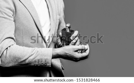 Man holding up bottle of perfume. Men perfume in the hand on suit background. Man in formal suit, bottle of perfume, closeup. Fragrance smell. Fashion cologne bottle. Copy space. Copy space.