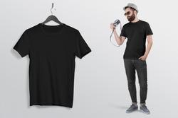man holding vintage camera in black crew neck t shirt hand in pocket wearing back denim jeans pant hanging t shirt on hanger