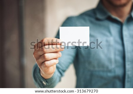 Man holding white business card on concrete wall background #313679270