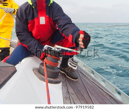 Man holding winch with rope on sailing boat
