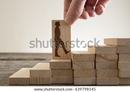 Man holding with his fingers wooden domino with shape of businessman walking up stairs to climb up career ladder. #639798145
