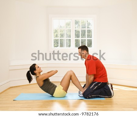 Man holding woman's feet down as she does sit up exercises.