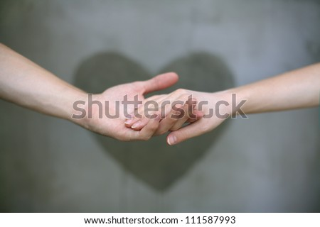 Man holding woman's hand with a heart painted wall in background