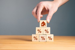 man holding wooden blocks with percent and house