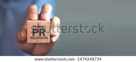 Man holding wooden cube. Pr- Public Relations Stockfoto ©