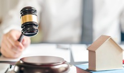 Man holding wooden gavel hitting on sound block, wooden gavel and house for real estate, bidding, buying or foreclosure house concept.