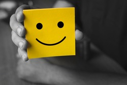 Man holding yellow card with smiley face - Customer service experience