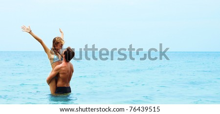 Man holding young woman in the hands in the blue sea