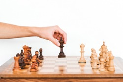 man holds a chess piece with his hand. Chess board. game of chess on a white background. chess tournament