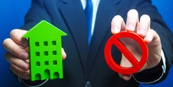 Man holds a green house and red prohibition symbol NO. Prohibition of operation. Denial of insurance payment. Bank refuses to provide a mortgage loan. Housing problems. Confiscation pledged property.