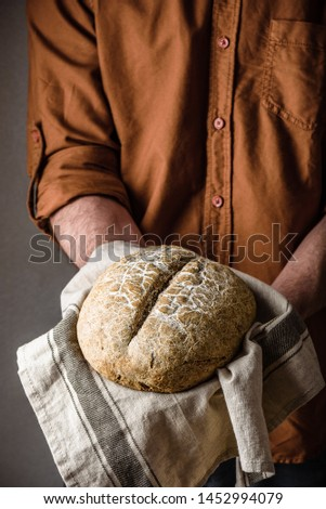 Man holds a loaf of freshly baked rye bread