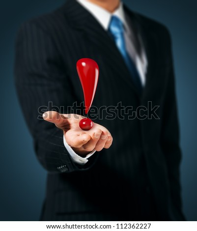 Man holds an exclamation mark in a hand