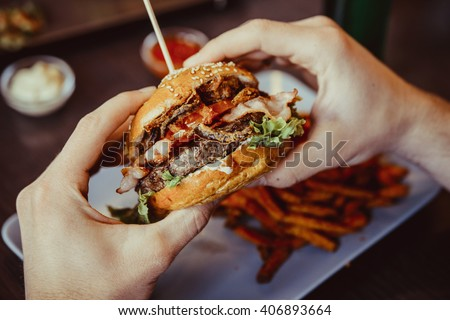 man holds burger with hands and sweet potato fries  and dips on background in cafe