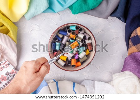 Man holds fork with spool of thread under the bowl with spools in fabric multi-colored frame on grey background #1474351202