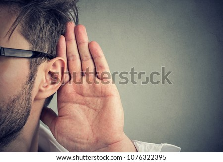man holds his hand near ear and listens carefully isolated on gray wall background