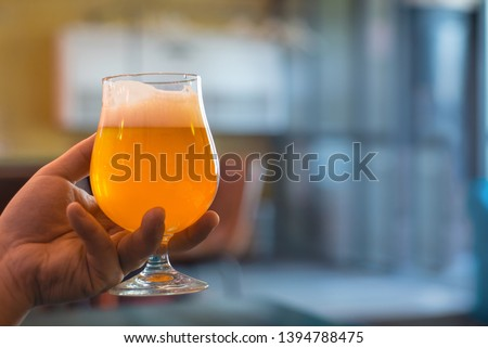 man holds in his hand a glass of craft beer Stok fotoğraf ©