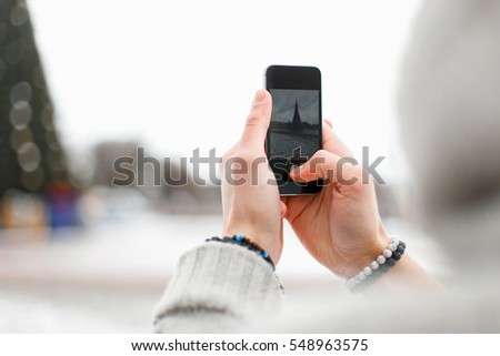 Man holds in his hands the phone and takes a picture. Christmas tree, winter holidays