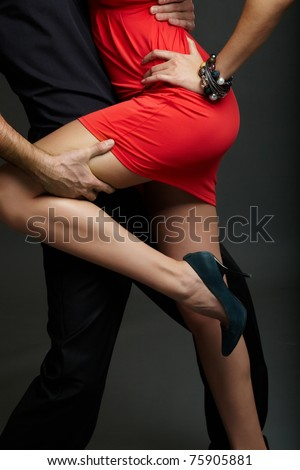 Man holds leg of female in red dress and high-heeled shoes - stock
