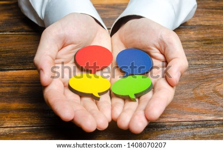 Man holds multicolored speech bubbles in his hands. Listen to other opinions and points of view, accepting criticism and comments. Reverse contact with customers and buyers. Freedom of speech.